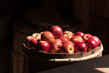 bushel of bright red apples, surrounded by dark interior