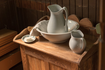white ceramic water jug and basin on wooden pioneer table
