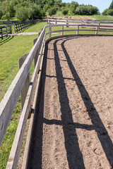 abstract shot of horse paddock rails in bright sun with shadows