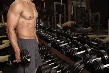 Sporty young man doing exercise with dumbbells in gym