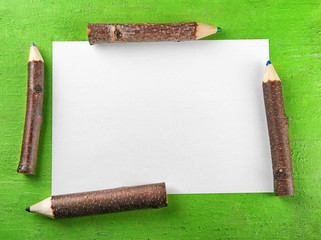 Blank sheet of paper and wooden pencils on green background
