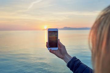 Frau fotografiert den Sonnenuntergang mit dem Handy