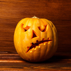 Scary Halloween pumpkin isolated on wooden background . Scary glowing face trick or treat. Concept of halloween pumpkin on wooden planks.