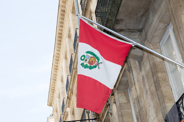 Peru flag on the mast waving against building in street