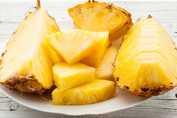 slices of a pineapple on white wooden background