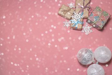 Christmas presents, white christmas balls at pink table. Flat lay with copy space. Christmas card in vanilla style