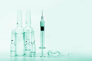 glass syringe in front of medicine bottles in green tone