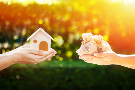 Loan or save for buy a house and real estate concept, Man and women hand holding money bags and a model home put together in the public park.