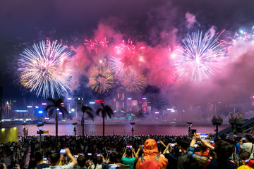 The crowd watching national day fireworks display in rain at waterfront of Victoria Harbour of Hong Kong