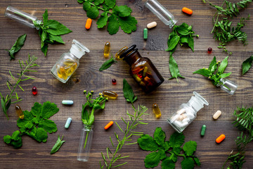 Herbal medicine pattern. Leaves, bottles and pills on wooden background top view