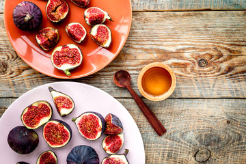 Plate of fresh blue figs and honey on wooden background top view copyspace