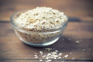 Cup of dry rolled oat flakes oatmeal on old wooden table