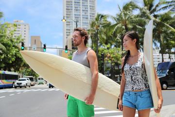 Honolulu Hawaii lifestyle surfers people walking in city with surfboards going to the beach surfing. Outside hawaiian surf living. Surfer couple crossing street. Waikiki, Honolulu, Oahu, Hawaii, USA.