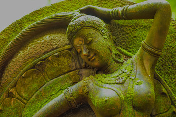 Statue of Goddess naked chest There are green moss on the body.