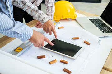Engineering is looking tablet on a blueprint. To prepare for field work