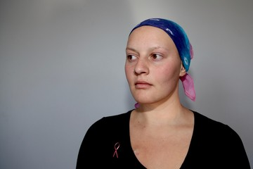 Young cancer patient in a headscarf looks to the side