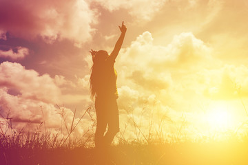 Silhouette young woman with raised hands standing on meadow on sunset, light effect