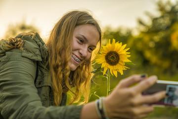 Eine junge Frau macht ein Selfie mit einer Sonnenblume