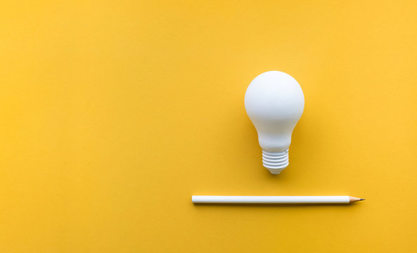 Creativity inspiration,ideas concept with lightbulb and pencil on pastel color background.Flat lay design.