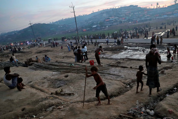A Rohingya child walks with the help of a stick at a refugee camp in Palang Khali near Cox's Bazar
