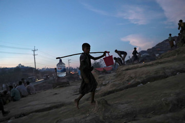 A Rohingya child carries water in the evening at a refugee camp in Palang Khali near Cox's Bazar