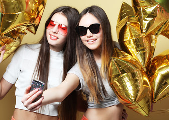 Two teenage girls friends with gold balloons  make selfie on a p