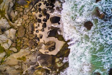Wall Mural - Aerial view looking down at sea waves hitting rocks