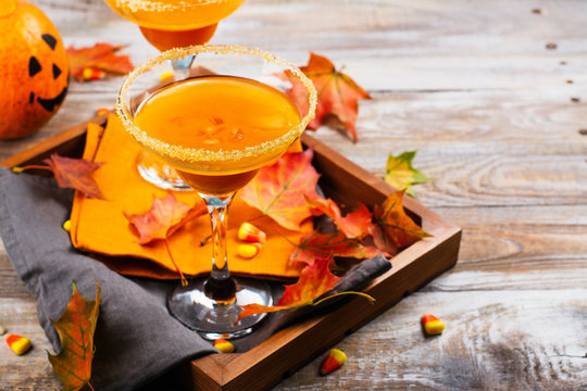 Autumn pumpkin martini cocktail with fall leaves on wooden tray. Copy space