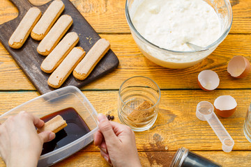 Photo of cooking tiramisu, human hands with savoyardi cookies