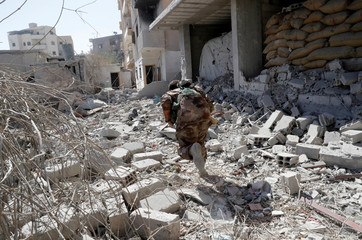 A member of Syrian Democratic Forces runs for cover from the sniper fire of the Islamic State militants near the stadium in Raqqa