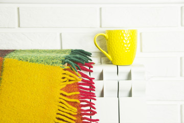 background - a brick wall with a white battery on which there is a multicolored plaid plaid and there is a yellow cup with tea. Copyspace