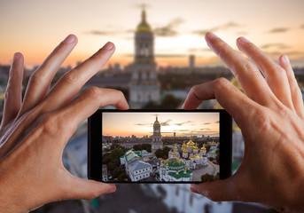 Travel concept. Hands making photo of Kiev Pechersk Lavra, Kiev, Kyiv, Ukraine.
