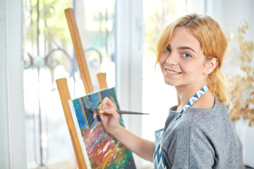 Young smiling girl paints on canvas with oil colors in own workshop. Window on the background. Art concept.