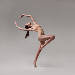 young beautiful ballet dancer in beige swimsuit