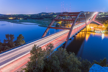 View of Pennybacker Bridge or 360 Bridge from limestone cliffs. A landmark in Austin, Texas, USA at blue hour with colorful car light trail in traffic. Top of Town Lake and Hill Country landscape.