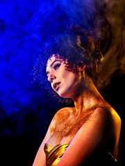Golden powder cosmetics on bare woman shoulders with decorative. Girl with curls on dark background. Woman at disco in gold mystical fog. Smoke from hookah. Exit of the soul from the body.