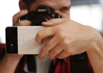 A man takes a photo of a Google Pixel 2 phone during a launch event in San Francisco