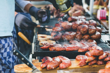 Street food in Amsterdam on sunday market. The cook is doing toasts with fried sausages and mustard.