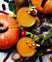 Fresh pumpkin smoothies on Halloween background with black candy, top view