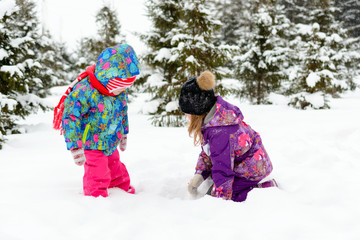 Girl with little sister playing in the snow among the pine trees