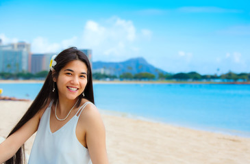 Teen girl sitting on Hawaiian beach, Diamond Head in background