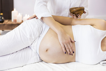 Young pregnant woman have massage treatment at spa