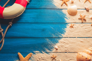 Wall Mural - beach scene concept with sea shells and starfish on a blue wooden background