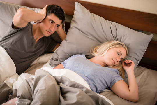 Young man annoyed by the snoring of his partner sleeping in bed at night