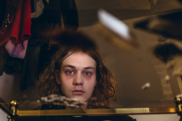 Low-angle view portrait of an addicted teenage boy staring while experiencing psychotropic effects caused by snorting cocaine
