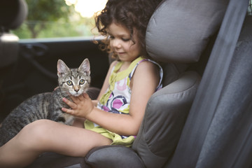 Little girl sitting in a car with a cat on her lap