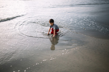 Little 4 year old kid wallowing and playing with water on the shore