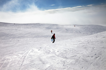 Skiers and snowboarders downhill on snow slope