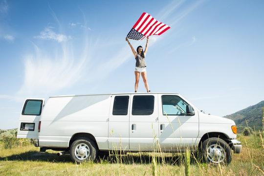 Woman holding American flag on van roof