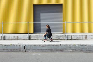 Teenage boy skateboarding on urban sidewalk